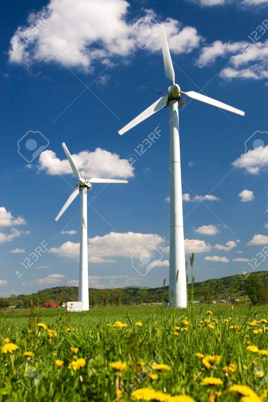 Windmills against blue sky with white clouds and yellow flowers on the ground Stock Photo - 3010588