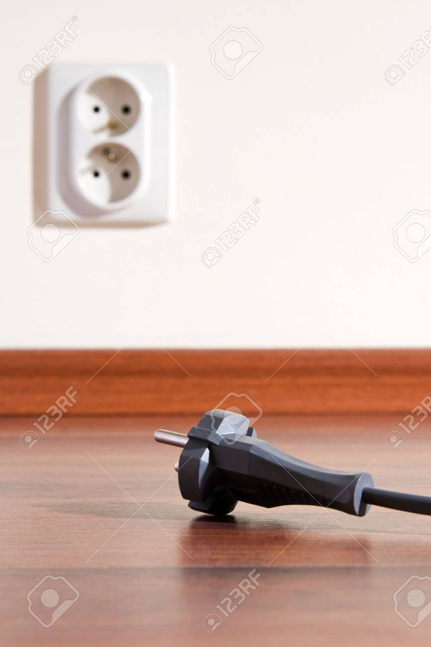 Two pin plug on the floor and electrical outlet in background Stock Photo - 3133853