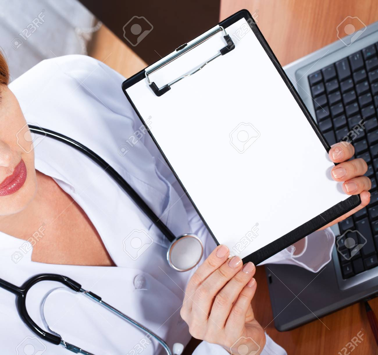 Female doctor showing blank clipboard Stock Photo - 17890292