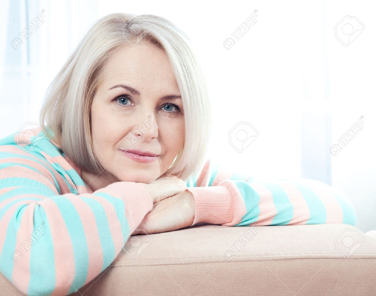 Active beautiful middle aged woman smiling friendly and looking into the camera at home. Woman's face close up. - 55650273
