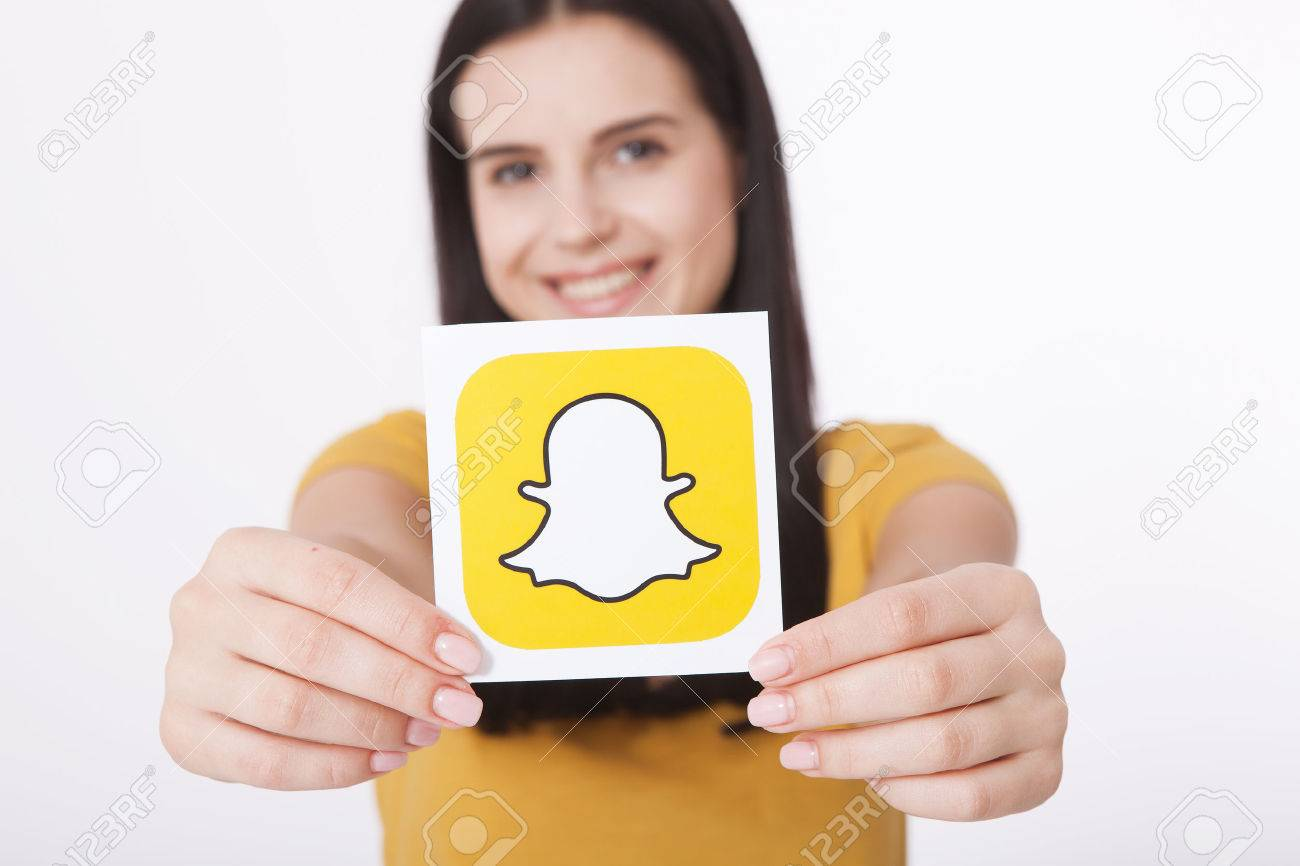 Kiev, Ukraine - August 22, 2016:Woman Hands holding Snapchat logo icon printed on paper. Snapchat is a popular social media application for sharing messages, images and videos - 84459382