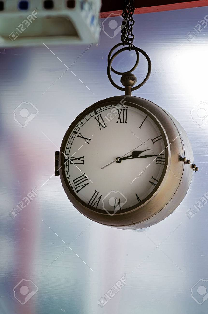 Wall clock on a massive chain hanging on a wooden construction wall clock on a massive chain hanging on a wooden construction with a blurred glass amipublicfo Choice Image