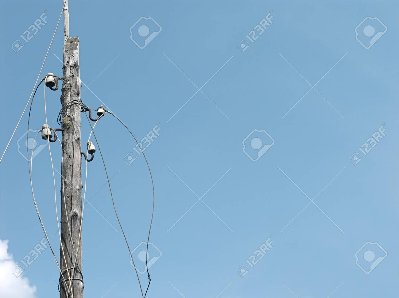 Electric Post With Disconnected Wires Against The Blue Sky ...