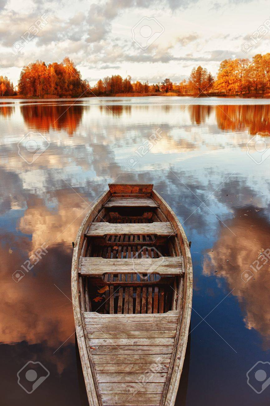 Wooden boat in the lake with the reflection of clouds Stock Photo - 13046648