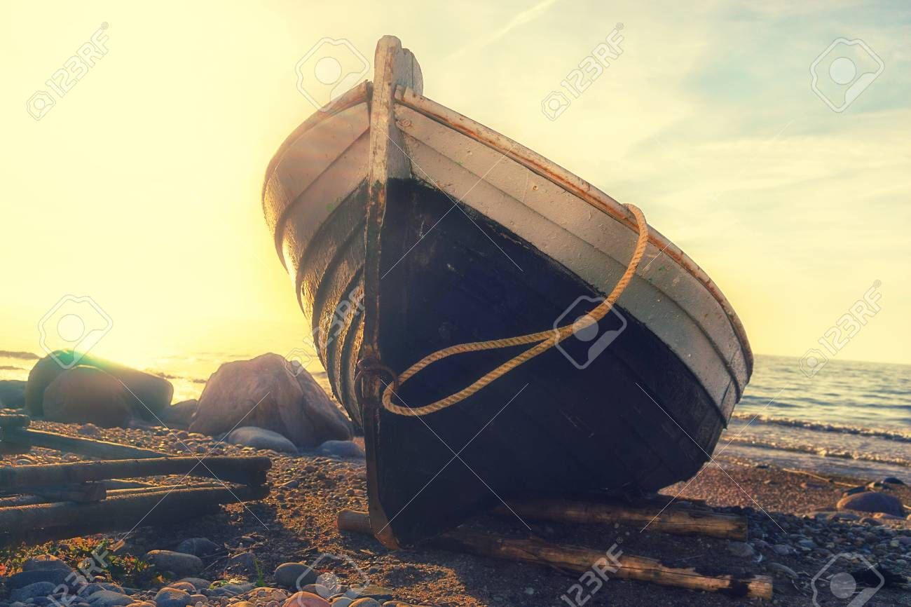 Fishing wooden boat with a rope on the rocky shore of the Baltic