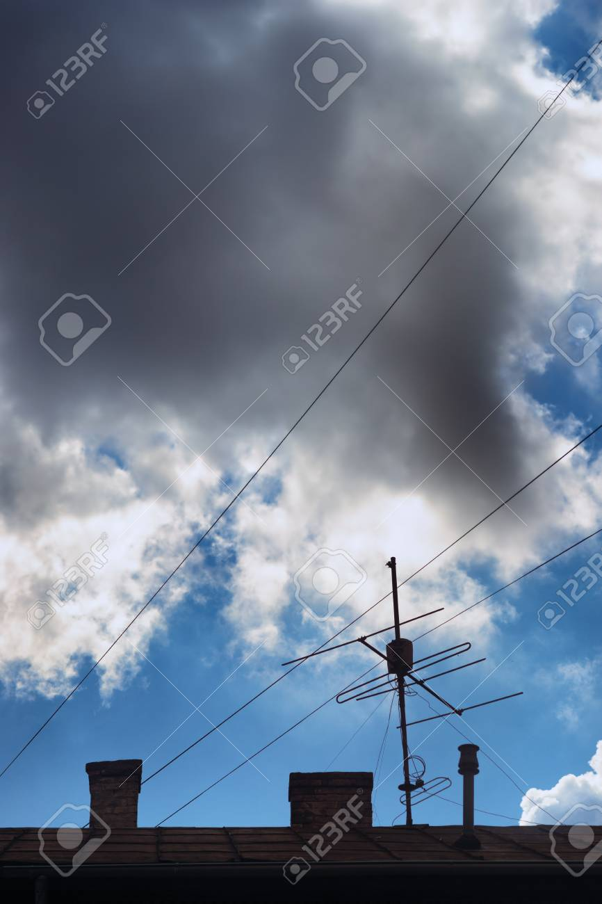 Clouds In The Blue Sky Above Roof Of House With Chimneys Antenna Wiring And