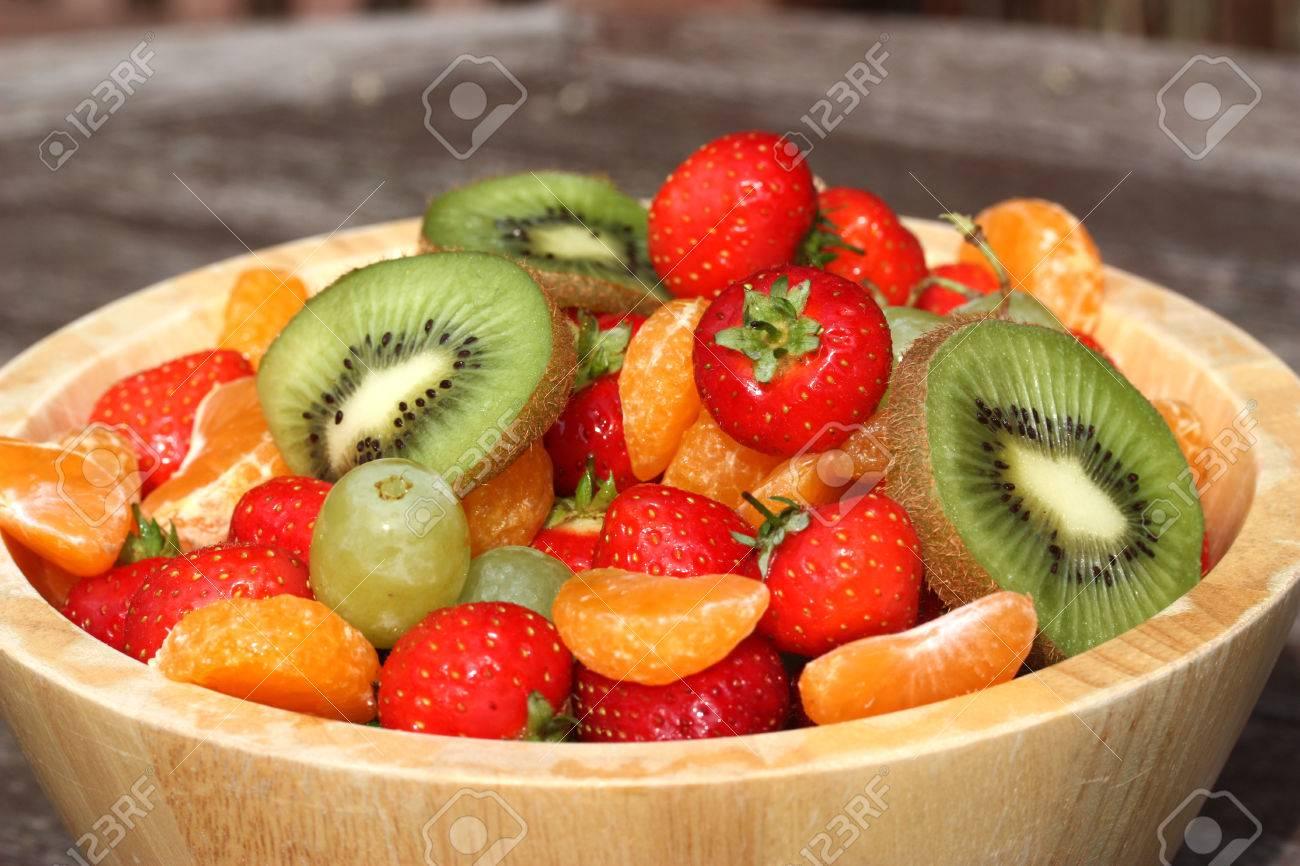 Bol de fruits d\'été dans un bol en bois rustique sur la table de jardin