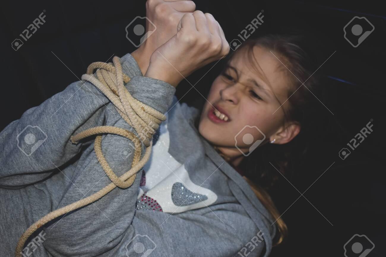 ropes on the hands of little victim girl. Violence against children. Kidnapping - 148271156