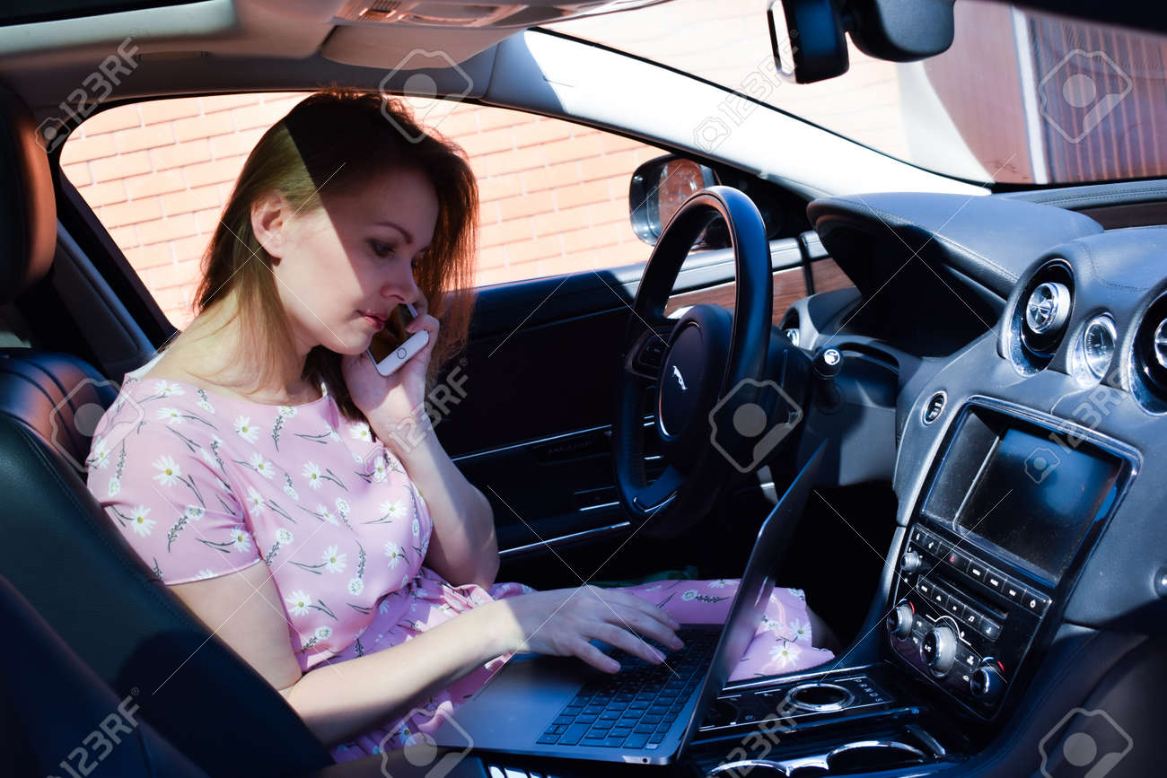 A woman working in car. Business woman with laptop in the car. A successful lady. Online jobs - 157097277