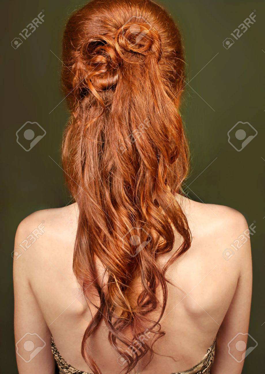Red long curly healthy hair of woman on green background Stock Photo - 12120553