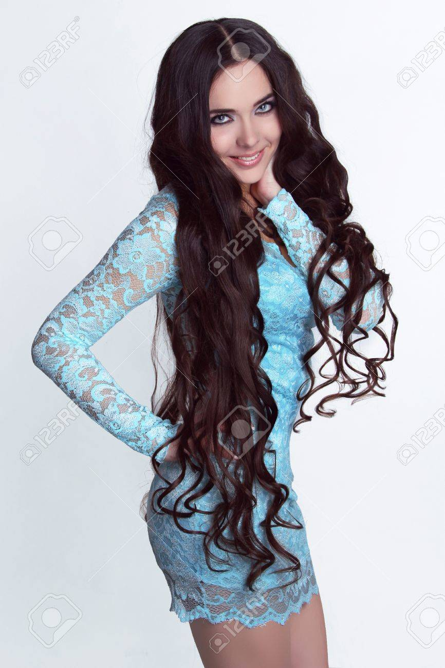 Happy smiling girl model. Healthy Long Curly Hair. Lady in blue dress Stock Photo - 16664782