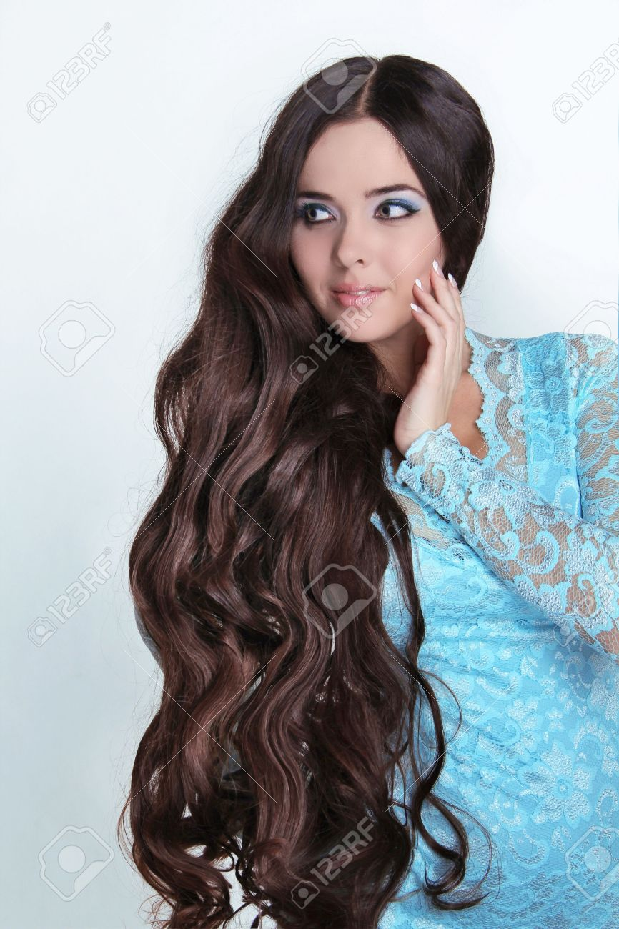 Beautiful Brunette Girl. Healthy Long Curly Hair. Lady in blue dress looking away Stock Photo - 16664725