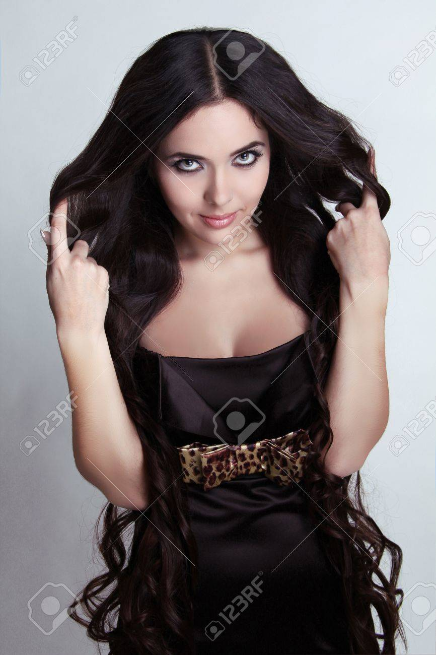 Smiling Brunette woman with long magnificent hair in black dress Stock Photo - 16664780