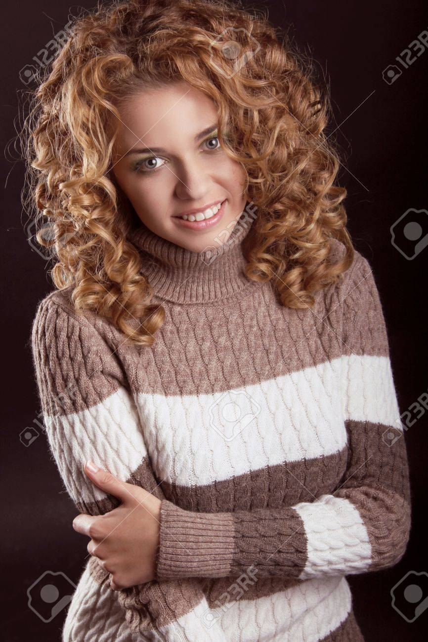 Attractive smiling woman wearing in sweater isolated on black background Stock Photo - 16960634