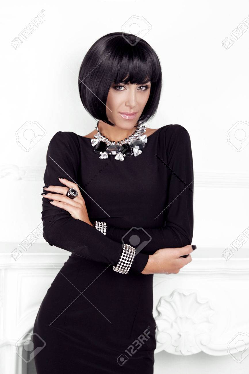 Vogue Style. Fashion Beauty Woman in sexy black dress. Brunette Lady with Black Short Hair Styling posing behind modern wall. Stock Photo - 23297952