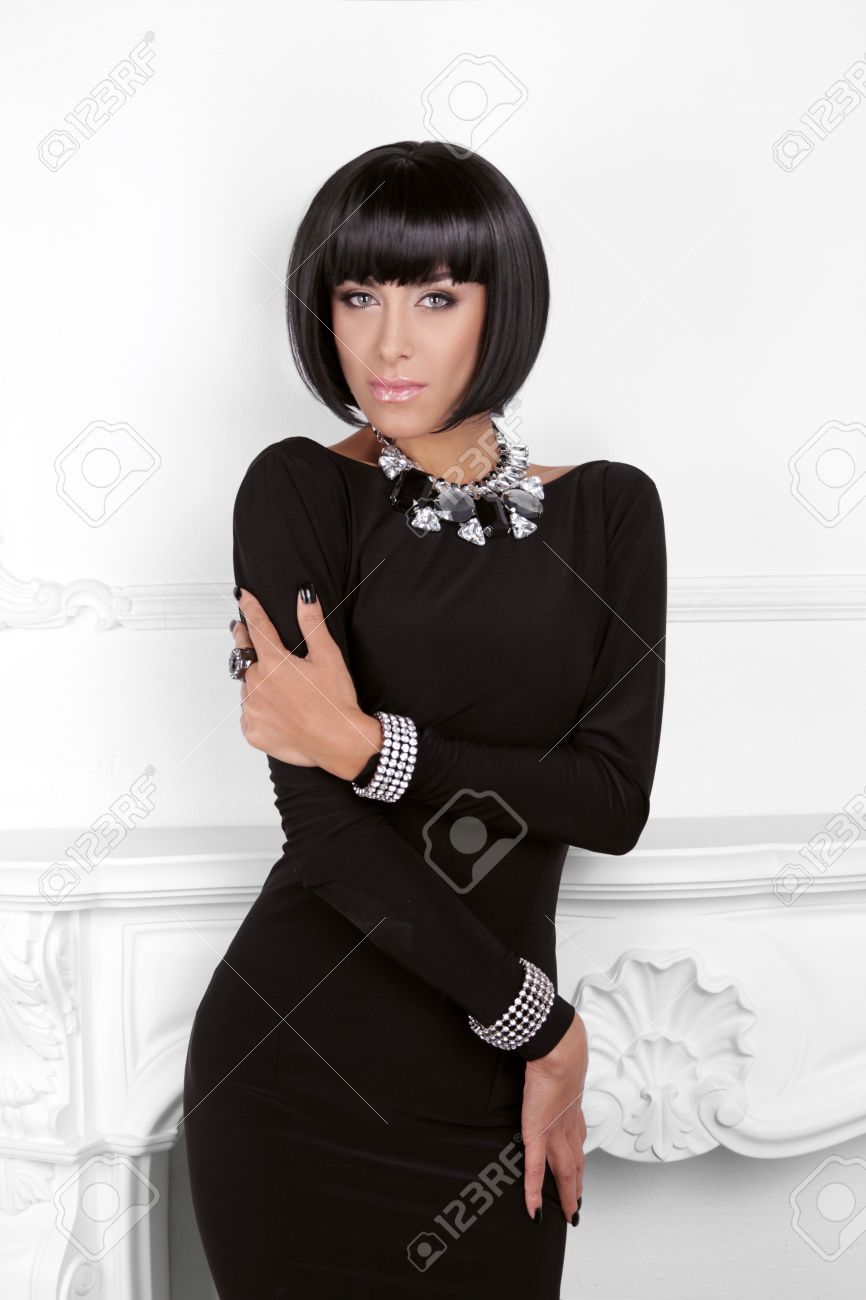 Vogue Style. Fashion Beauty Woman in sexy black dress. Brunette Lady with Black Short Hair Styling posing behind modern wall. Stock Photo - 23297948