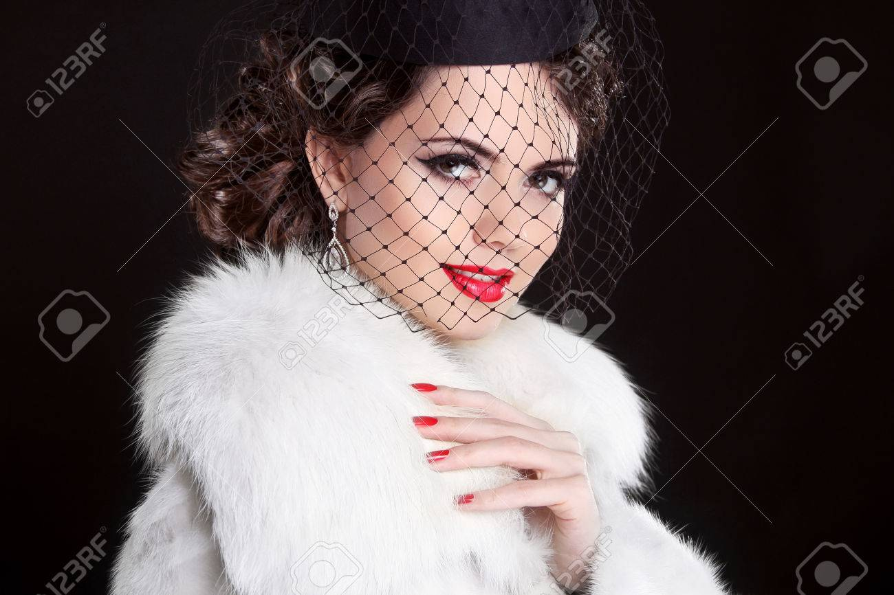Fashion Portrait of elegant retro woman wearing little hat with veil and white fur coat Stock Photo - 24661920