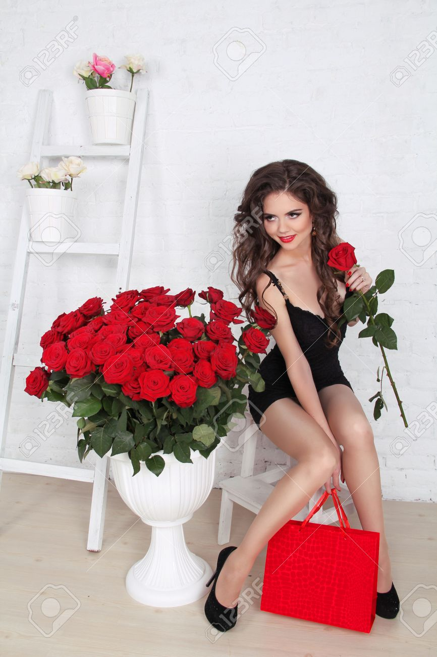 beautiful gorgeous smiling woman with bouquet of red roses and