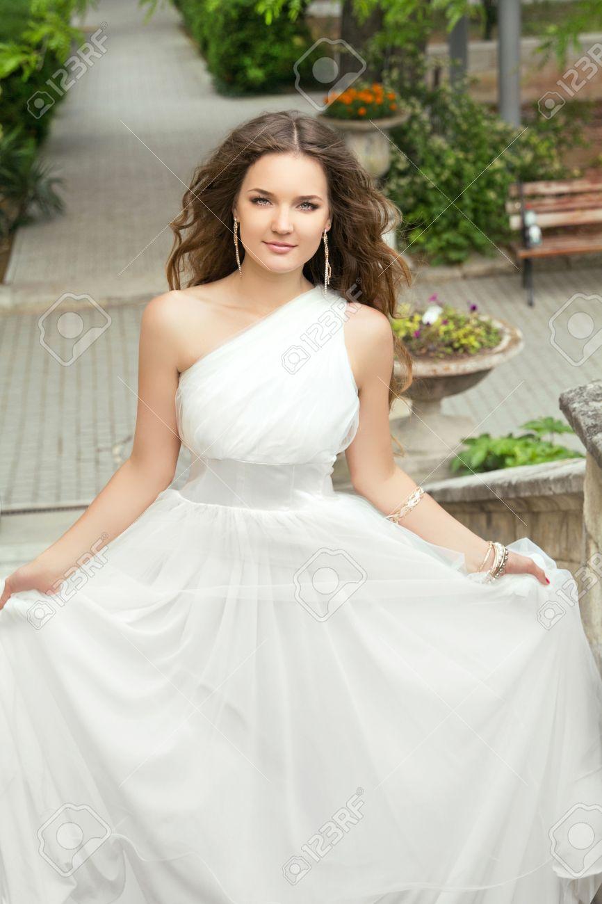 公園で膨大なスカートとウェディング ドレスの長いウェーブのかかった髪の魅力的な花嫁。