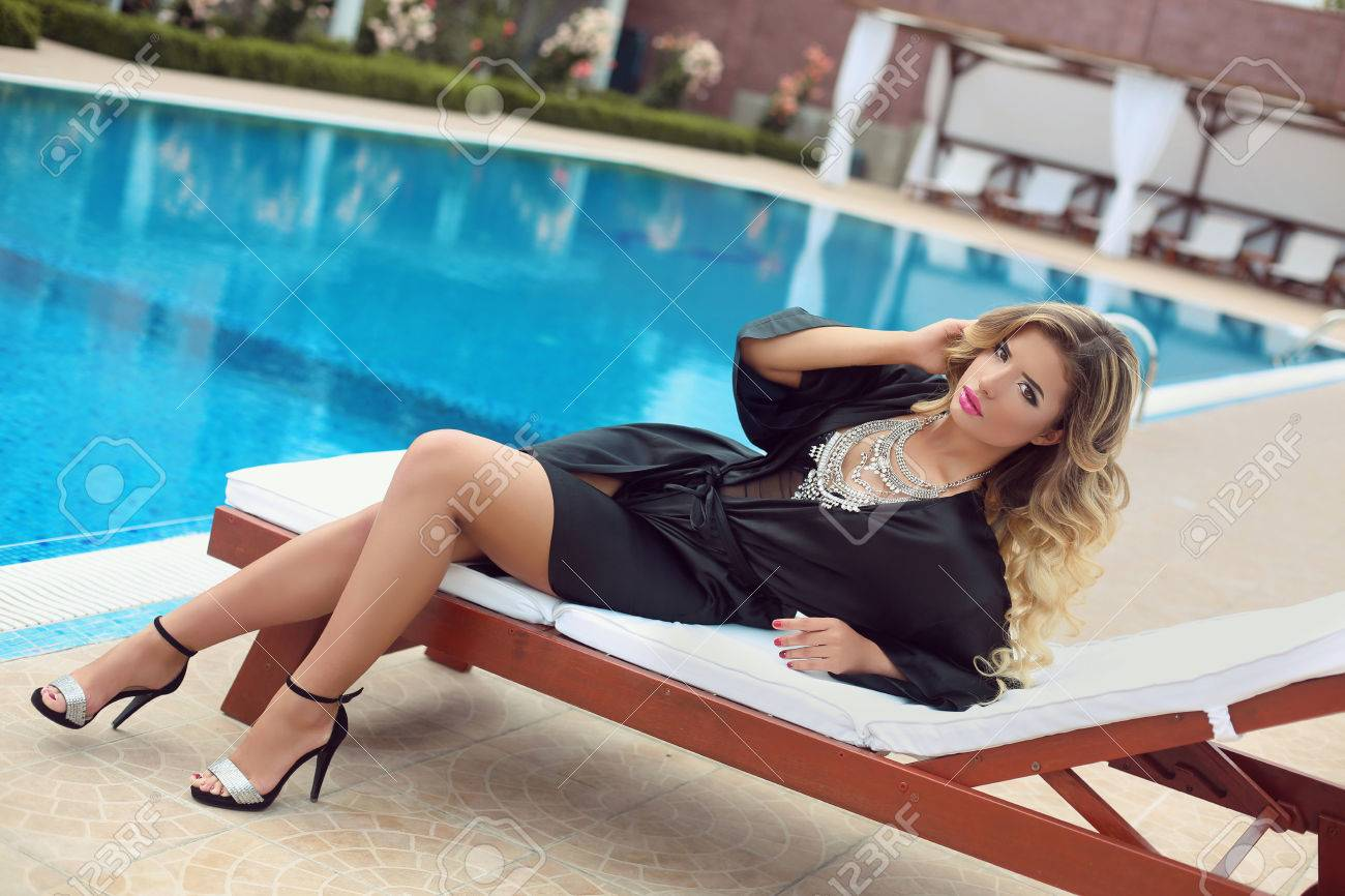 25186b0c85e ... summer holidays or travel vacations. Luxury resort sexy girl model in  fashion clothes relaxing on beach bed by swim pool.