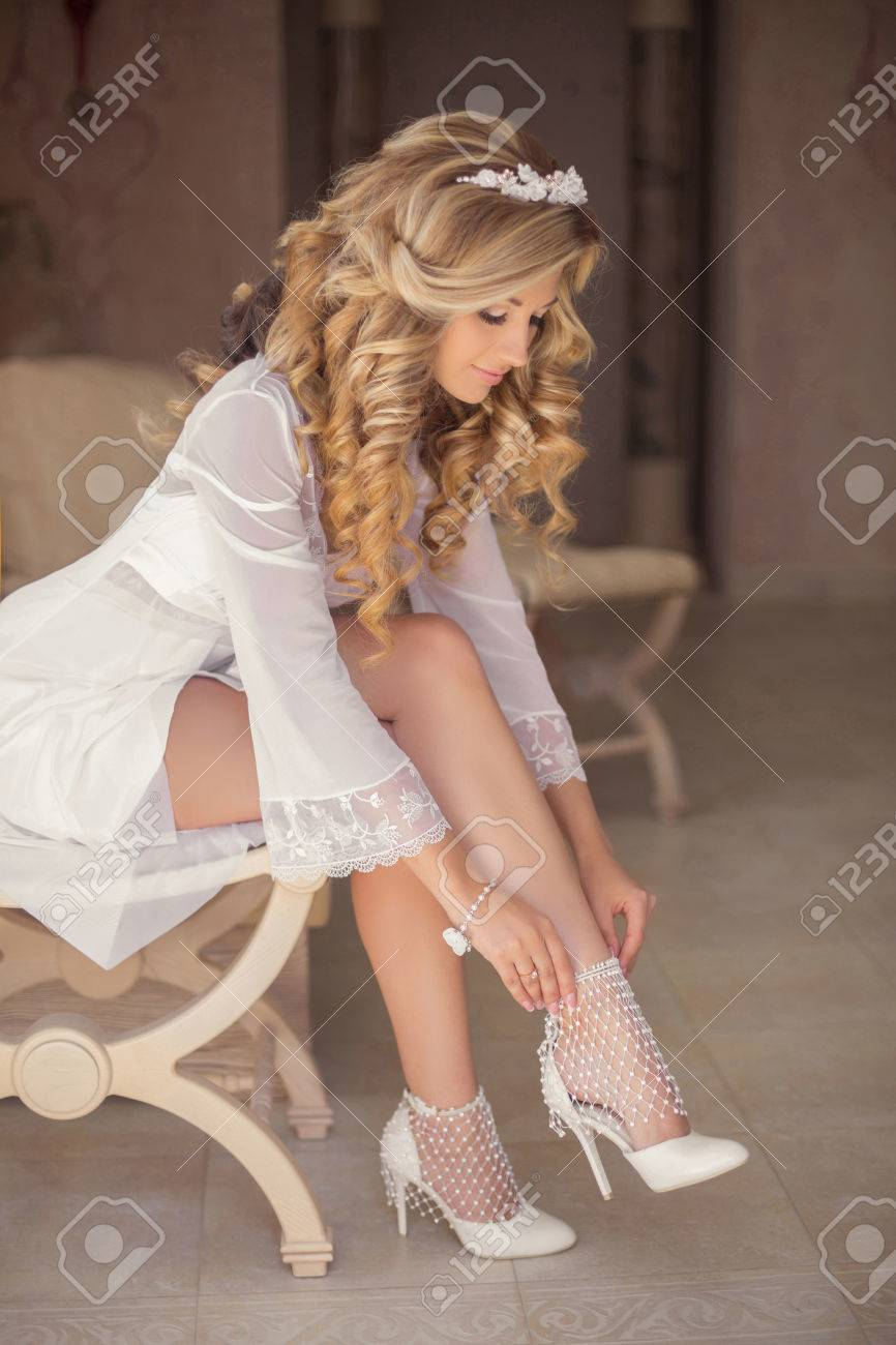 6dc07b420b84 Beautiful blonde bride wearing white wedding shoes, girl with curly hair  style sitting on modern