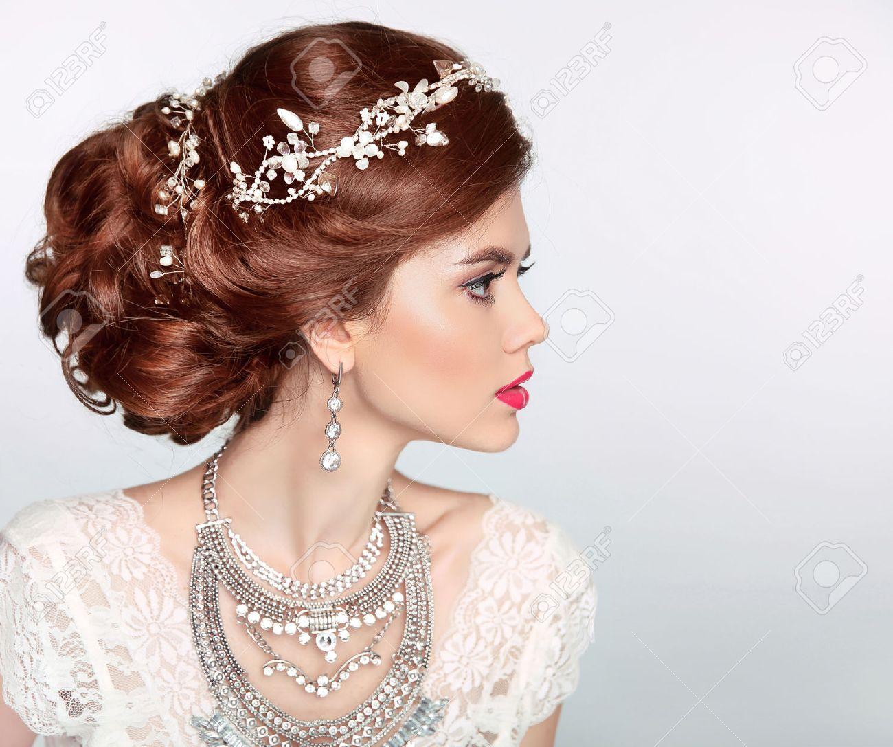Hochzeitsfrisur. Schöne Mode Braut Mädchen Model Porträt. Luxus-Schmuck.  Attraktive junge Frau mit roten Haaren.