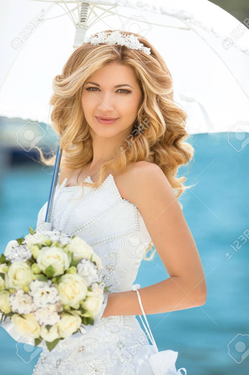 3e0cae501e Beautiful smiling bride girl in wedding dress with white umbrella and  bouquet of flowers against the