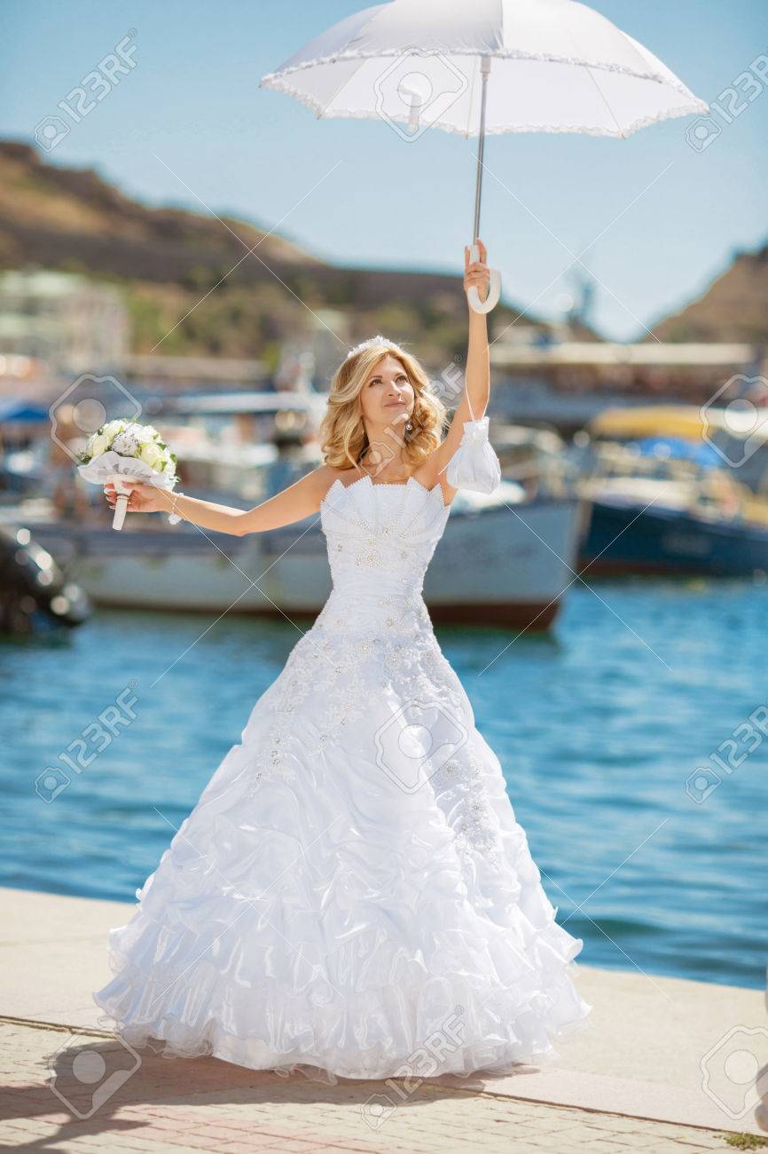fb918f9441 Beautiful smiling bride girl in wedding dress with white umbrella and  bouquet of flowers walking on