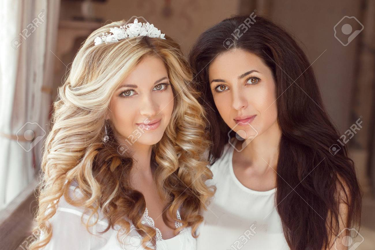 healthy hair two beautiful girls brunette stylist and smiling