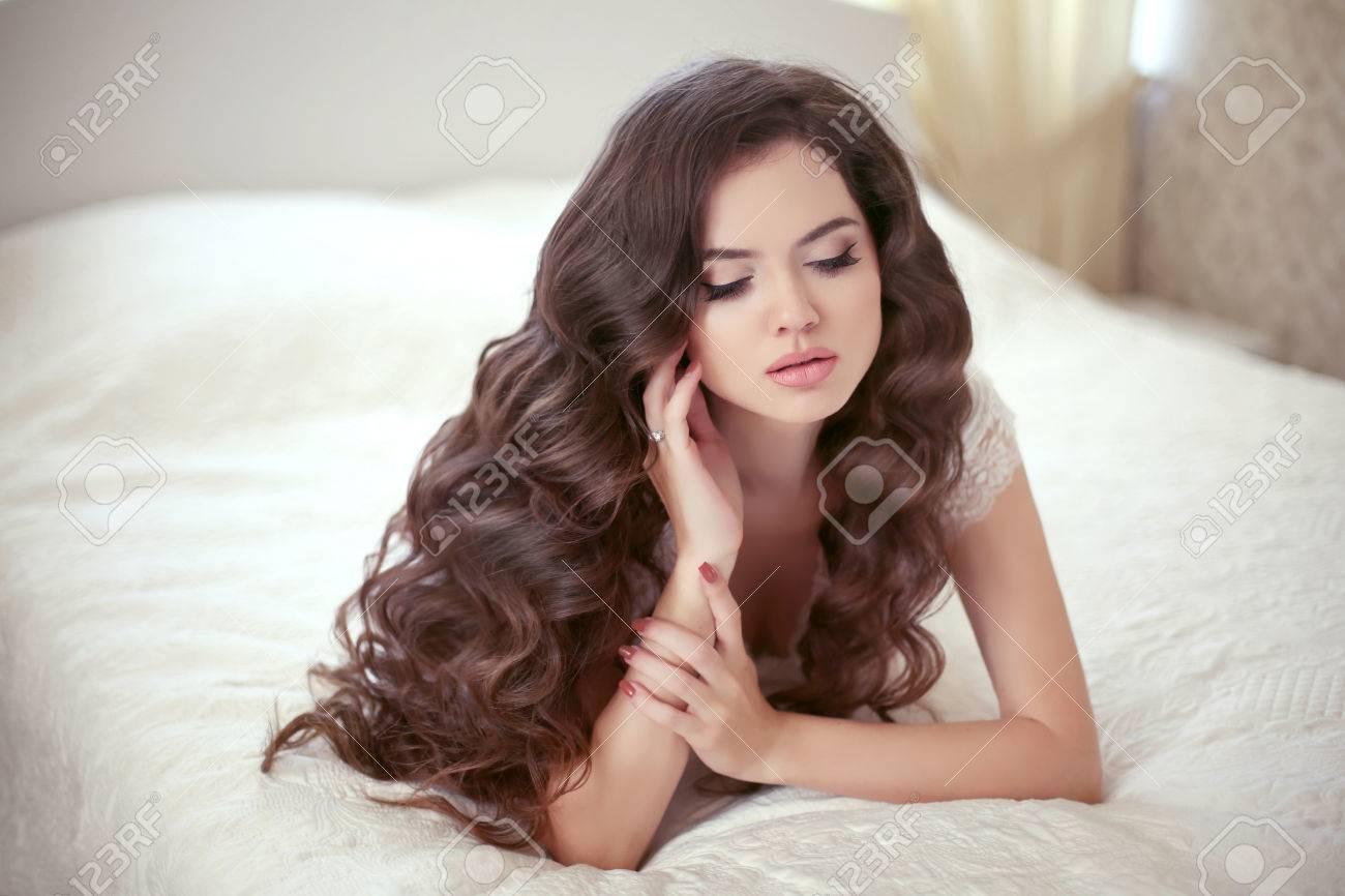 peinado ondulado la muchacha hermosa novia morena con el pelo rizado largo saludable y maquillaje