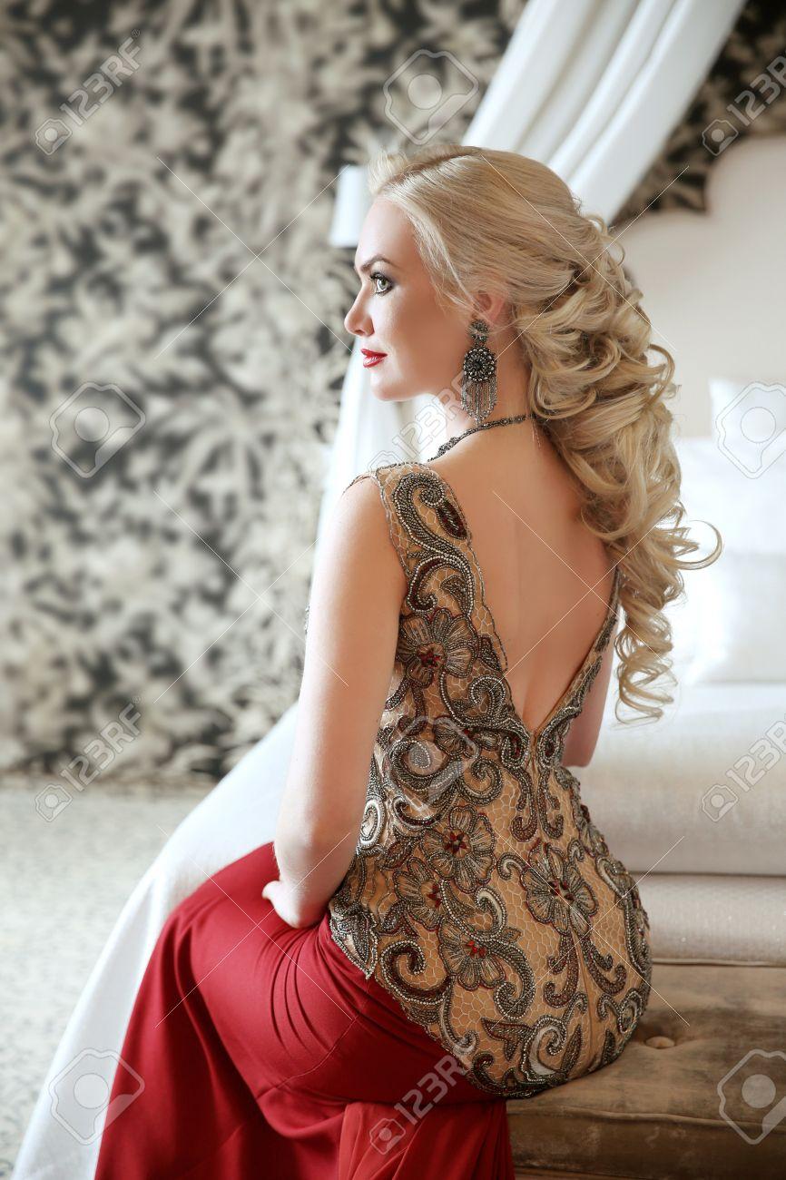 72233df03 Foto de archivo - Peinado elegante. Hermosa mujer rubia en vestido rojo  manera que se sienta en el sofá moderno en el lujoso apartamento interior  con ...