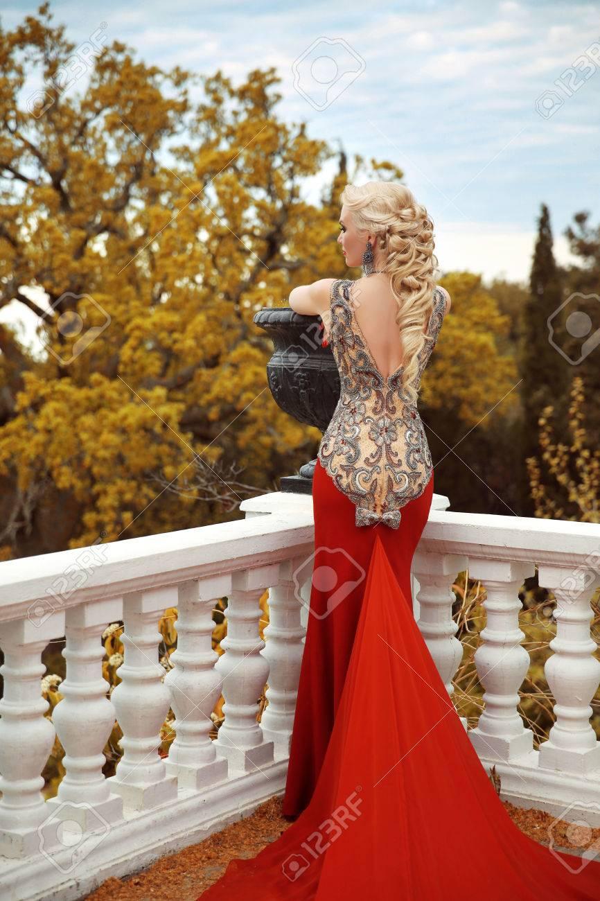 赤マーメイド ドレスでセクシーな戻って若い美女女性。長い巻き毛のエレガントな髪型とゴージャスなファッション  ブロンドの女の子モデル。屋外の秋のポートレート。