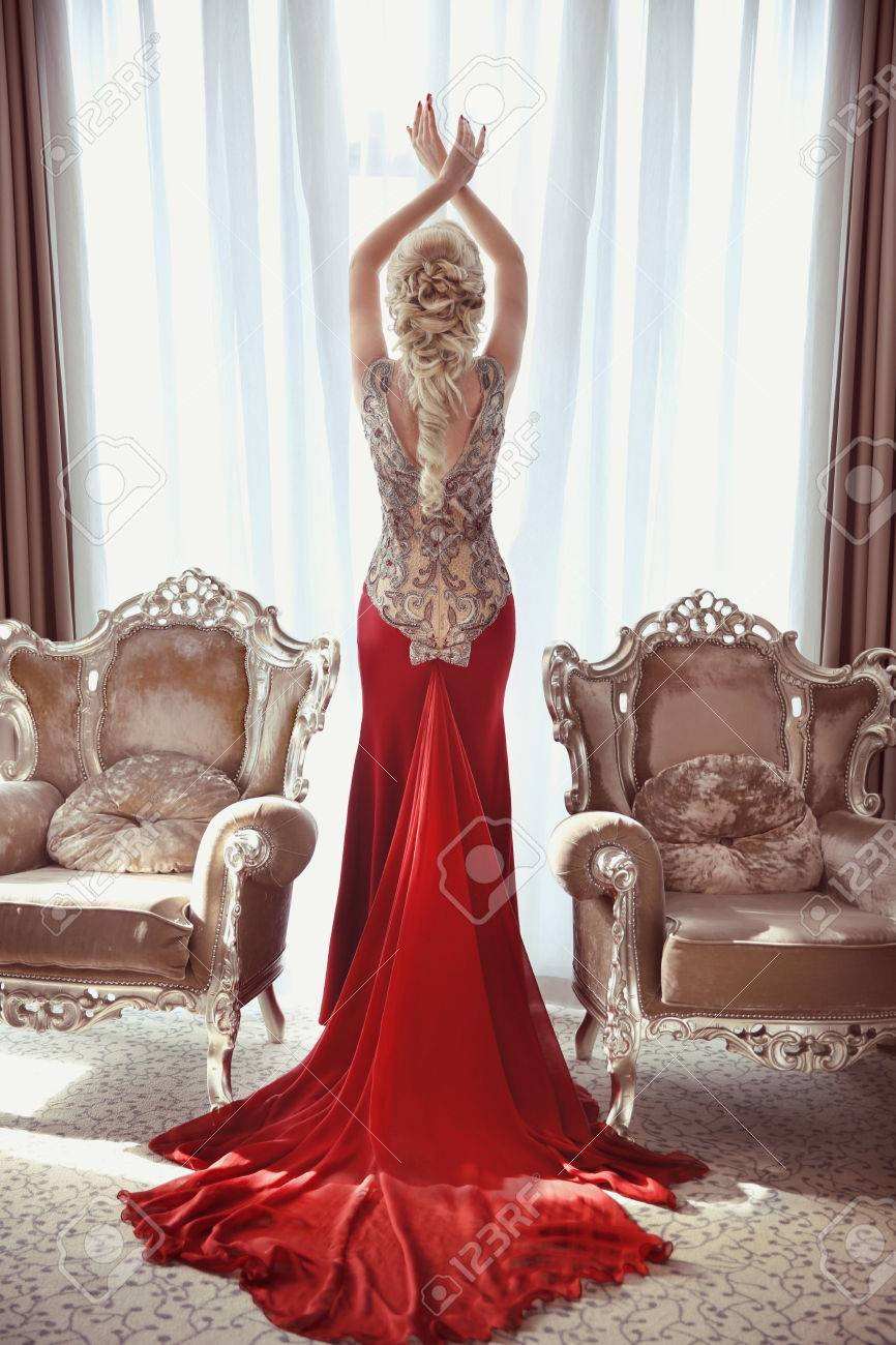 Traîne Modernes Face Indoor Avec Deux Élégante Longue Robe En Fauteuils De Blonde Rouge Entre Femme Portrait Posant Pied La nP08Owk