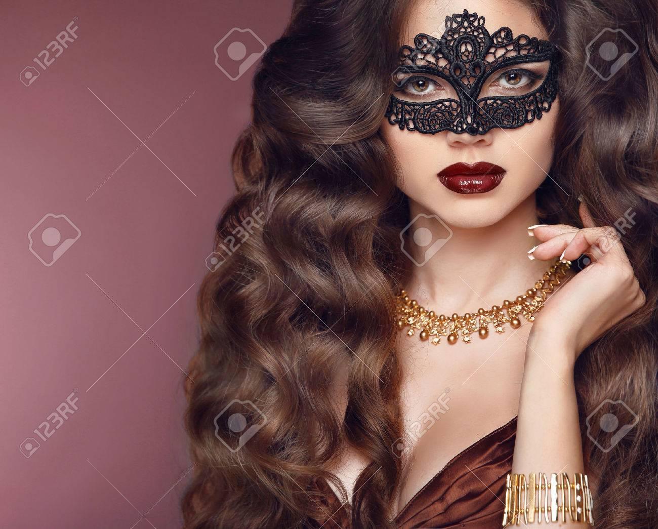 Healthy elegant hairstyle. Beautiful brunette girl model. Fashion golden jewelry. Beauty glamour woman wearing in venetian masquerade carnival mask. - 55684212