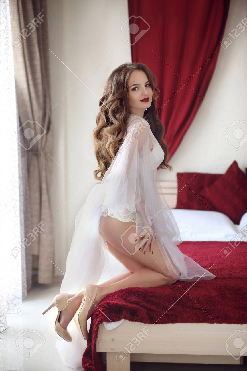 Beautiful sexy Bride wedding Portrait with curly hair style wearing in  white boudoir dressing gown posing