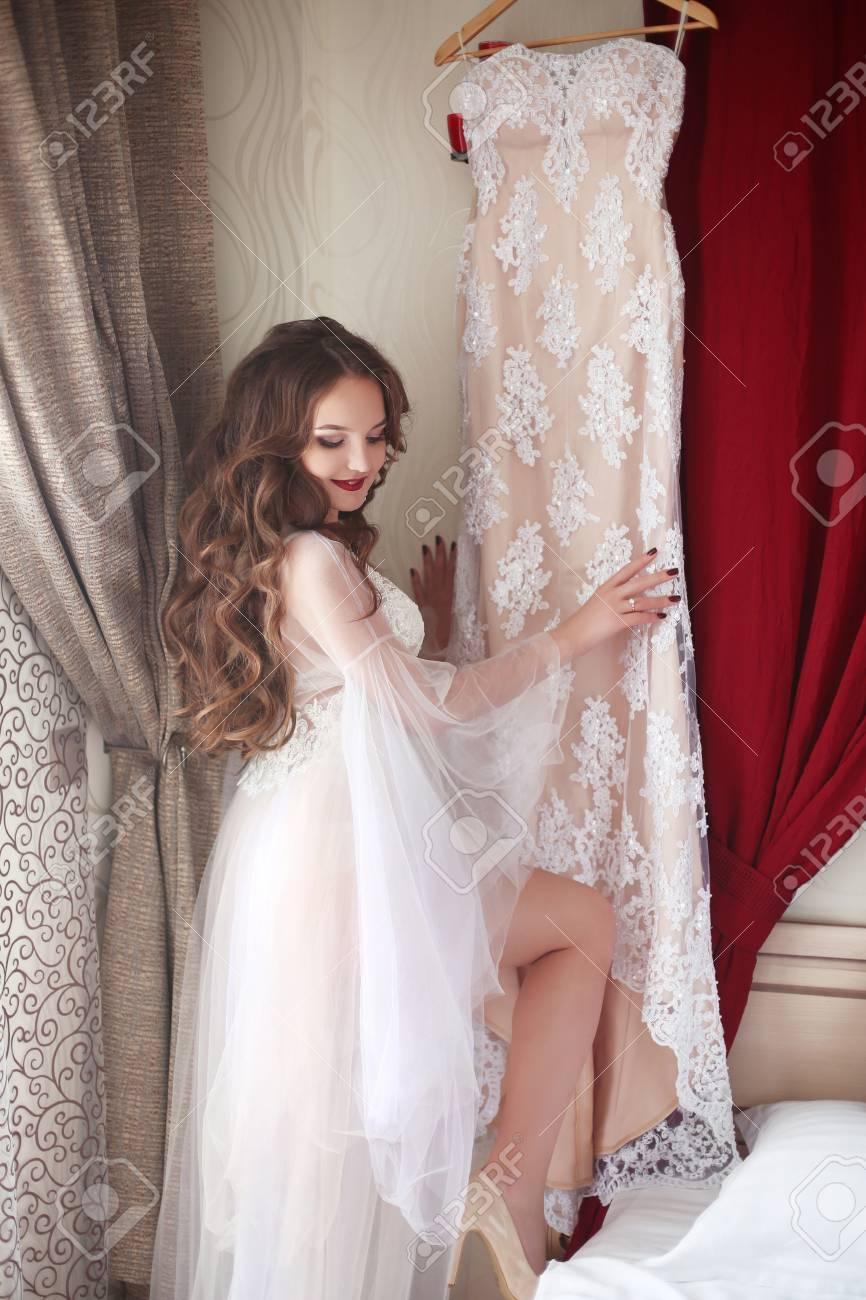 hochzeit vorbereitung. schöne brunettebraut in sexy unterwäsche lächelnd  bewundern die spitze brautkleid. boudoir. elegantes abendkleid.