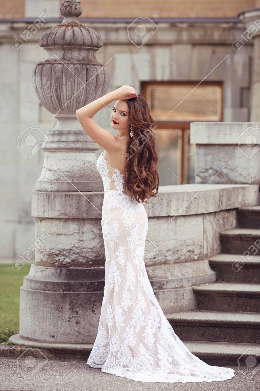 エレガントな花嫁の女性結婚式の肖像画、流行スタイル写真。ファッション ブルネット モデル花瓶彫刻によって白いマーメイド  ドレスでポーズします。長いウェーブのかかった髪。