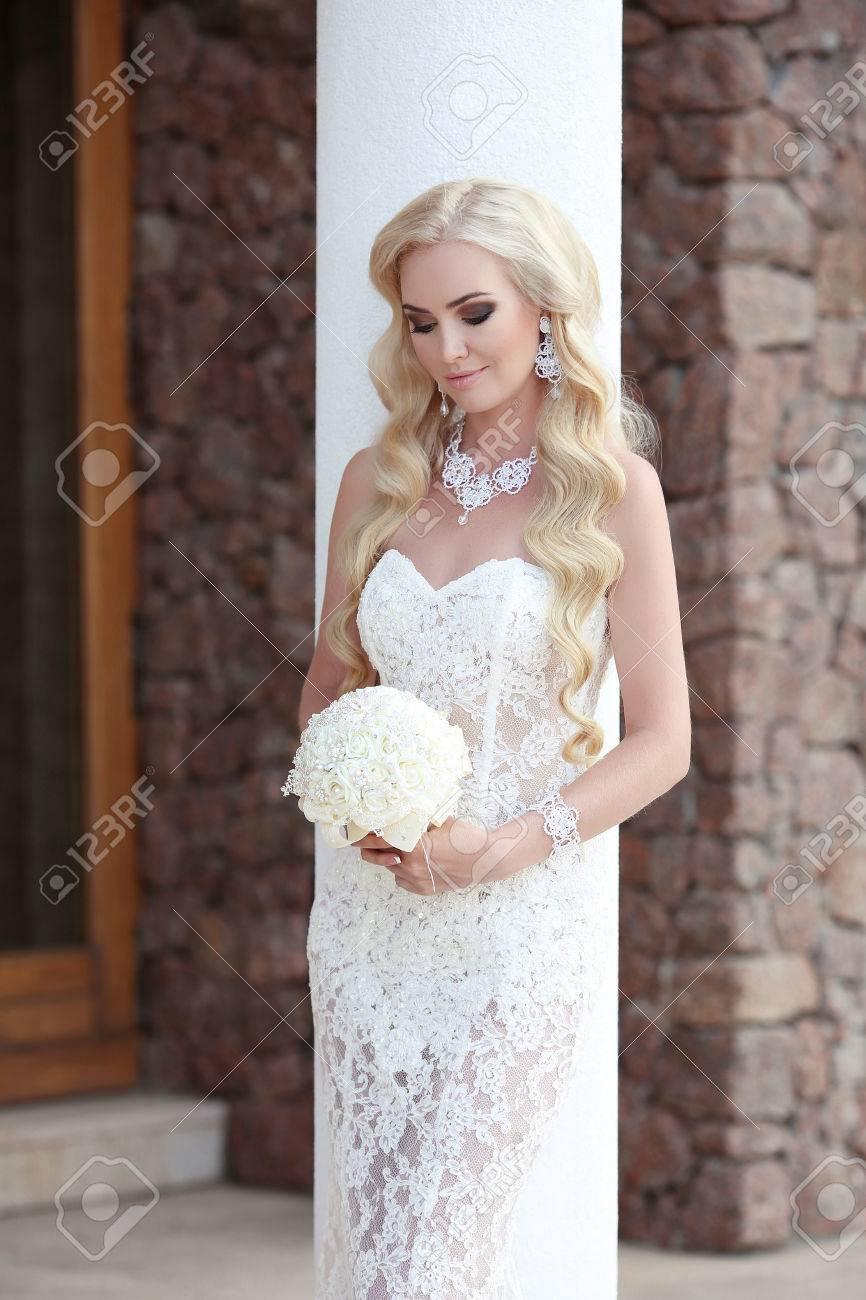beautiful bride wedding portrait holding bouquet posing in lace..