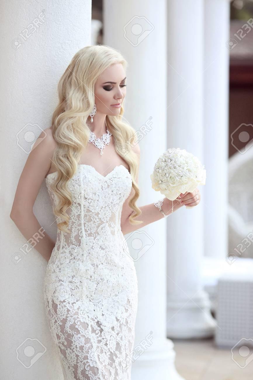 美しい花嫁の肖像画がウェディング ブーケ レースのマーメイド ドレスでポーズを保持します。メイク。ウェーブのかかった髪型、宝石のモデル、ファッション  モデル ゴージャスな美しさ、幸せな女の笑みを浮かべてします。