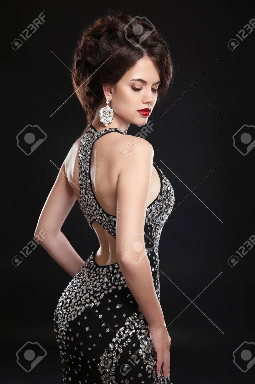 0c00215fff8e73 Mooie mode elegante vrouw in zwarte sexy jurk en dure sieraden.  Glamourfoto. Slank meisjesmodel
