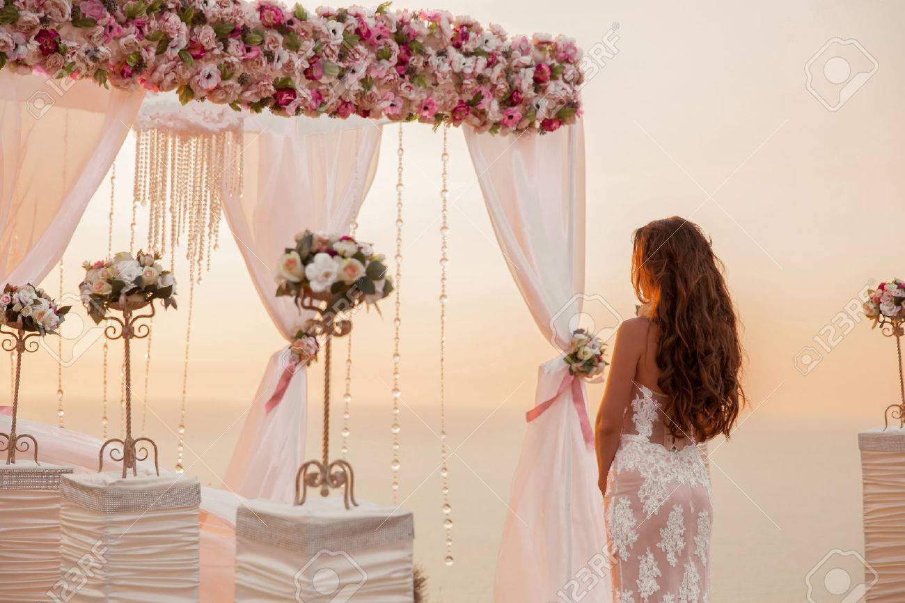 Wedding ceremony. Brunette bride standing by wreath arch with flower arrangement and white curtain on cliff above sea, outdoor summer photo. Bridal day. Sunset. - 63649241