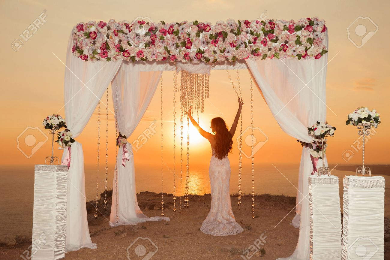 Sunset. bride silhouette. Wedding ceremony arch with flower arrangement and white curtain on cliff above sea, outdoor summer photo. - 63649051