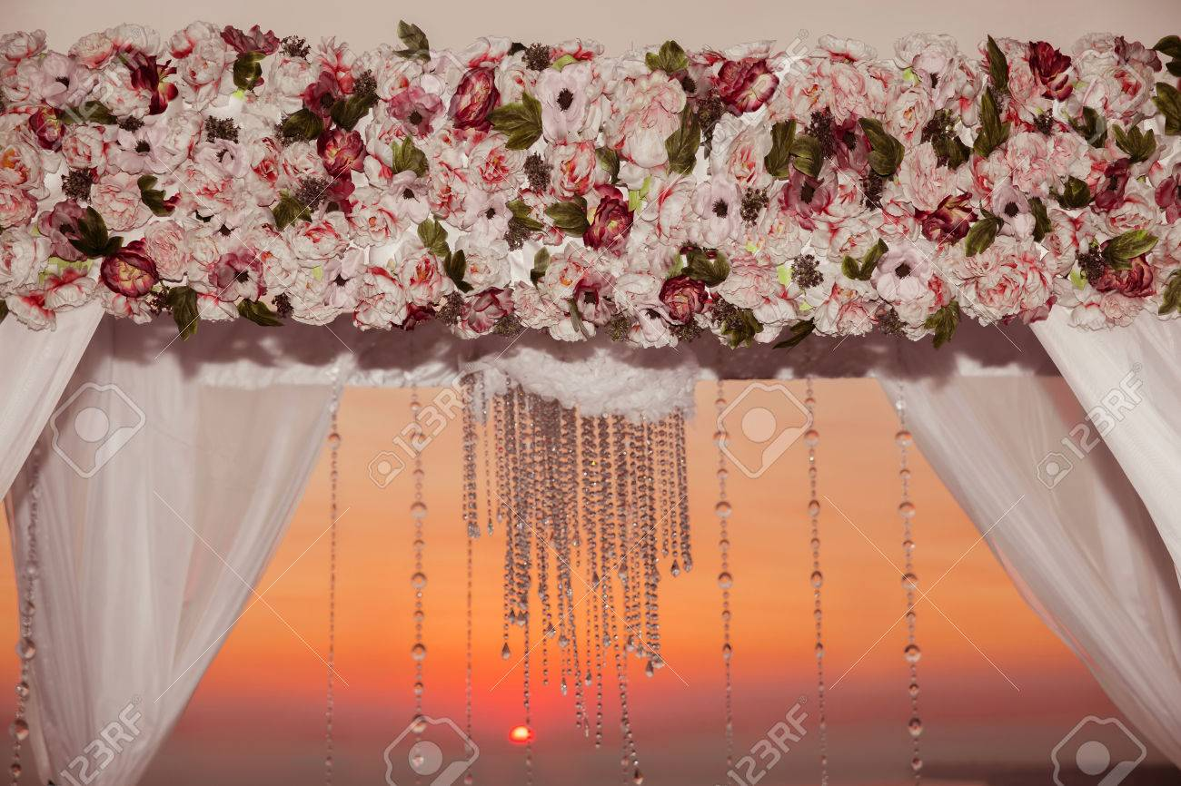 Wedding Ceremony Arch Decor Closeup With Flower Arrangement And Crystals Chandelier Decorated White Curtain Above Sea Outdoor Photo