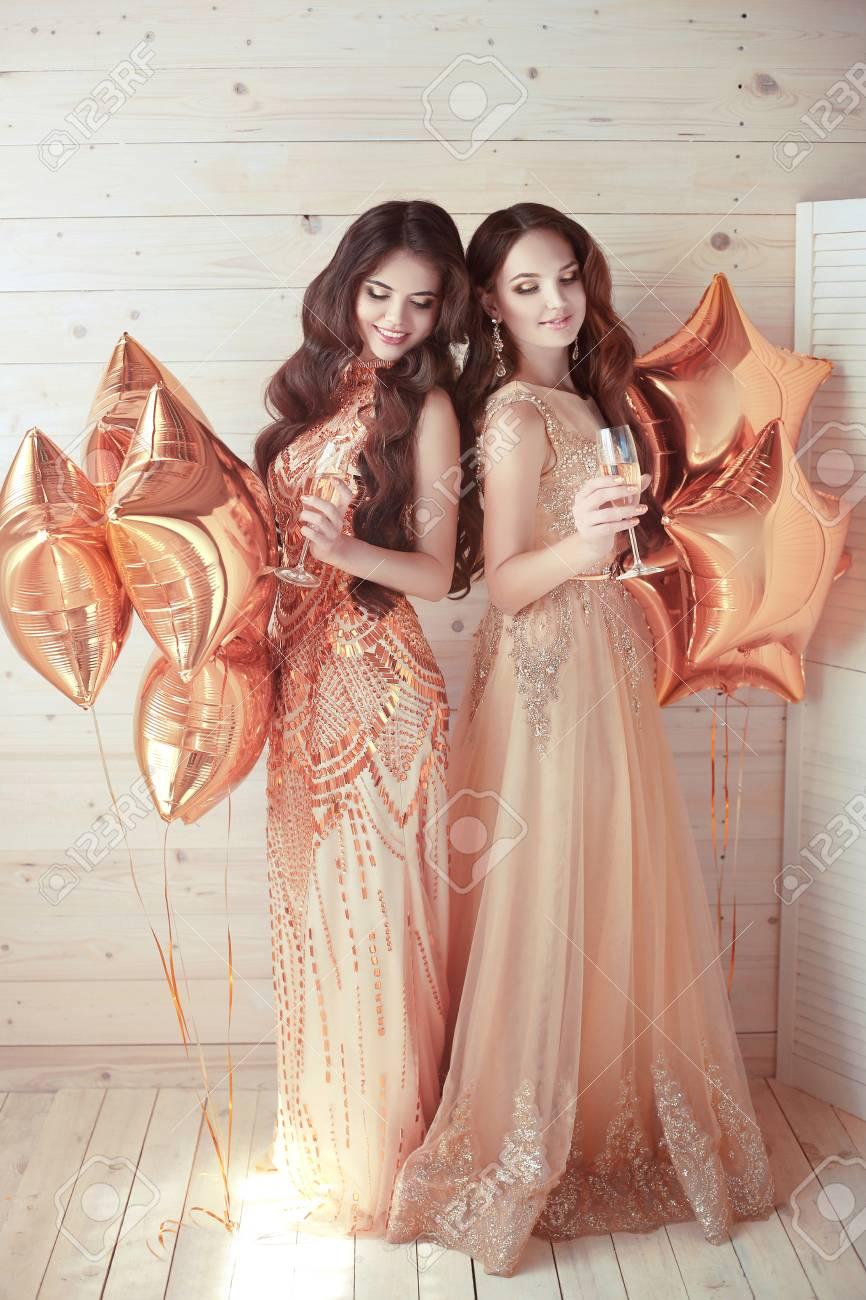 Zwei Mädchen Auf Party. Schöne Junge Frauen In Eleganten Goldenen ...