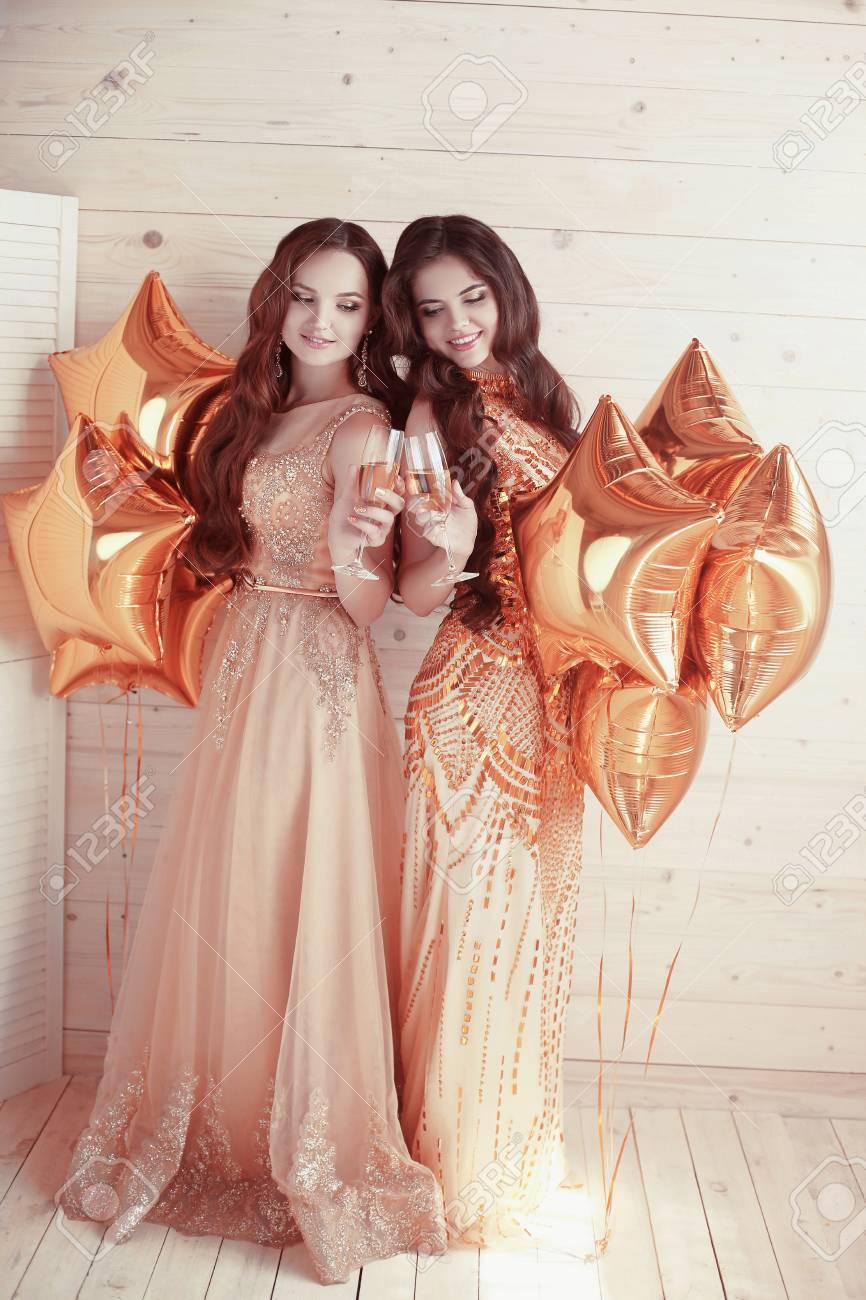 baebd07f1854 Due donne felici congratulazioni più stelle d oro palloncini. amici ragazza  elegante in abiti lunghi d oro della moda.