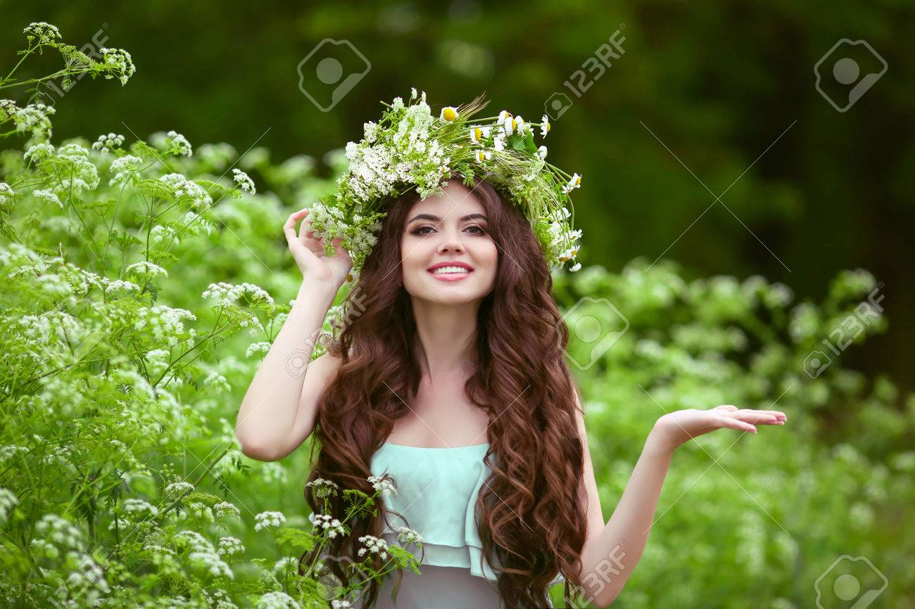 Portrait of smiling young woman in green spring park with open empty palm hand for copy space. Beautiful female with healthy long curly hair posing outdoors. - 68506470