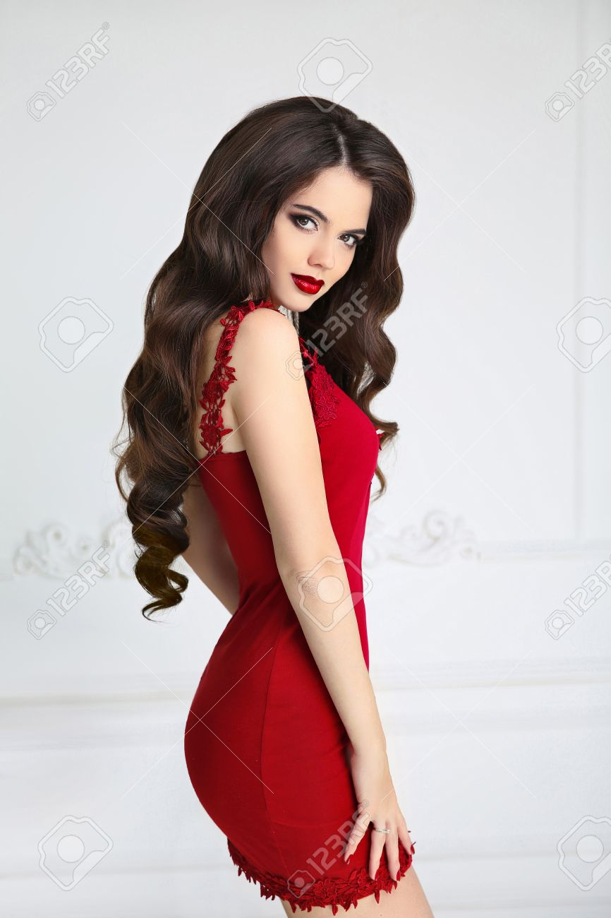 47bf1979981e Elegant brunette sexy woman in fashion red dress. Attractive girl model  with red lips makeup