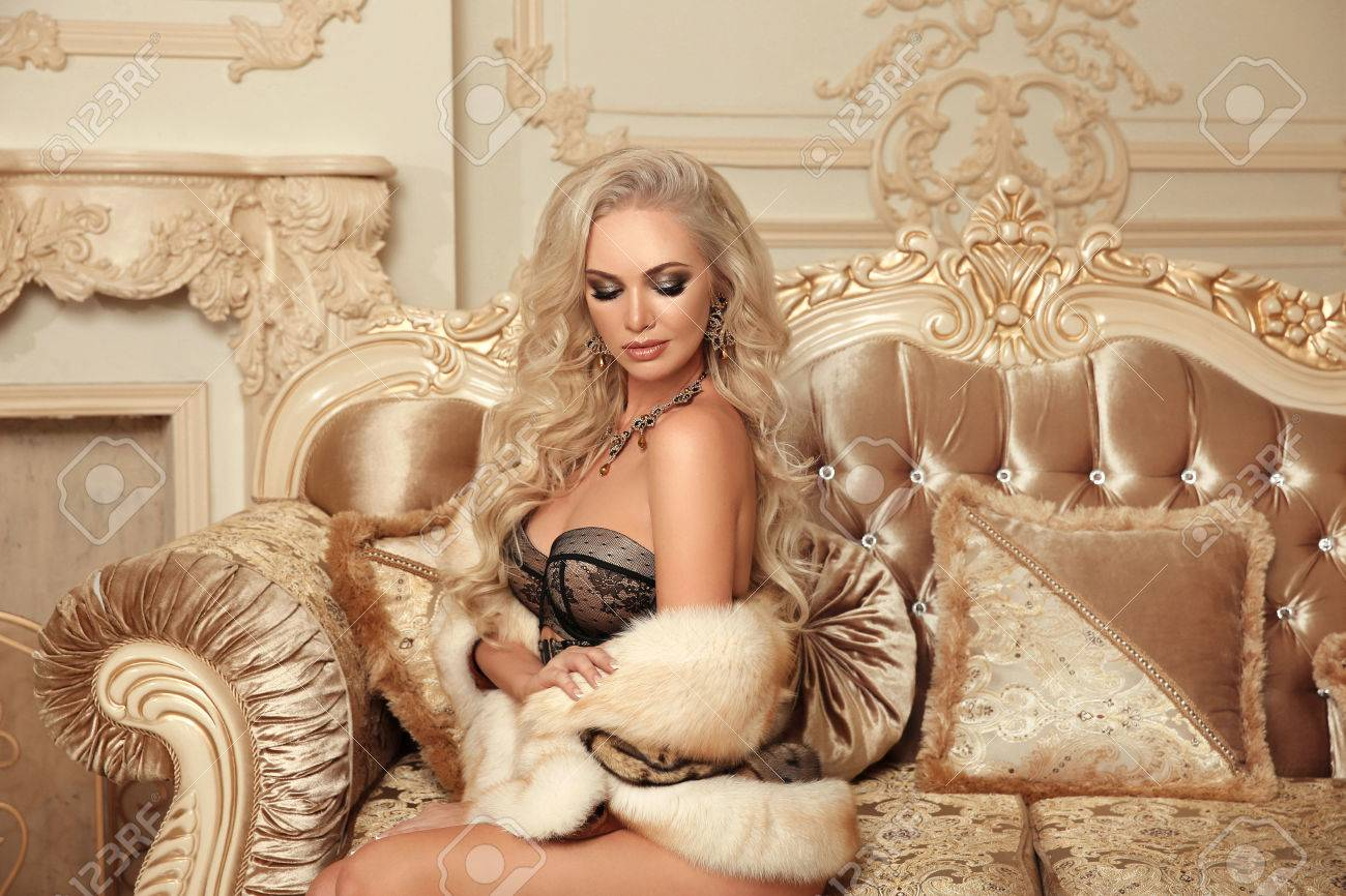 30accfe3f Beautiful alluring gorgeous woman in sexy lingerie and fur coat posing on  royal sofa in luxury