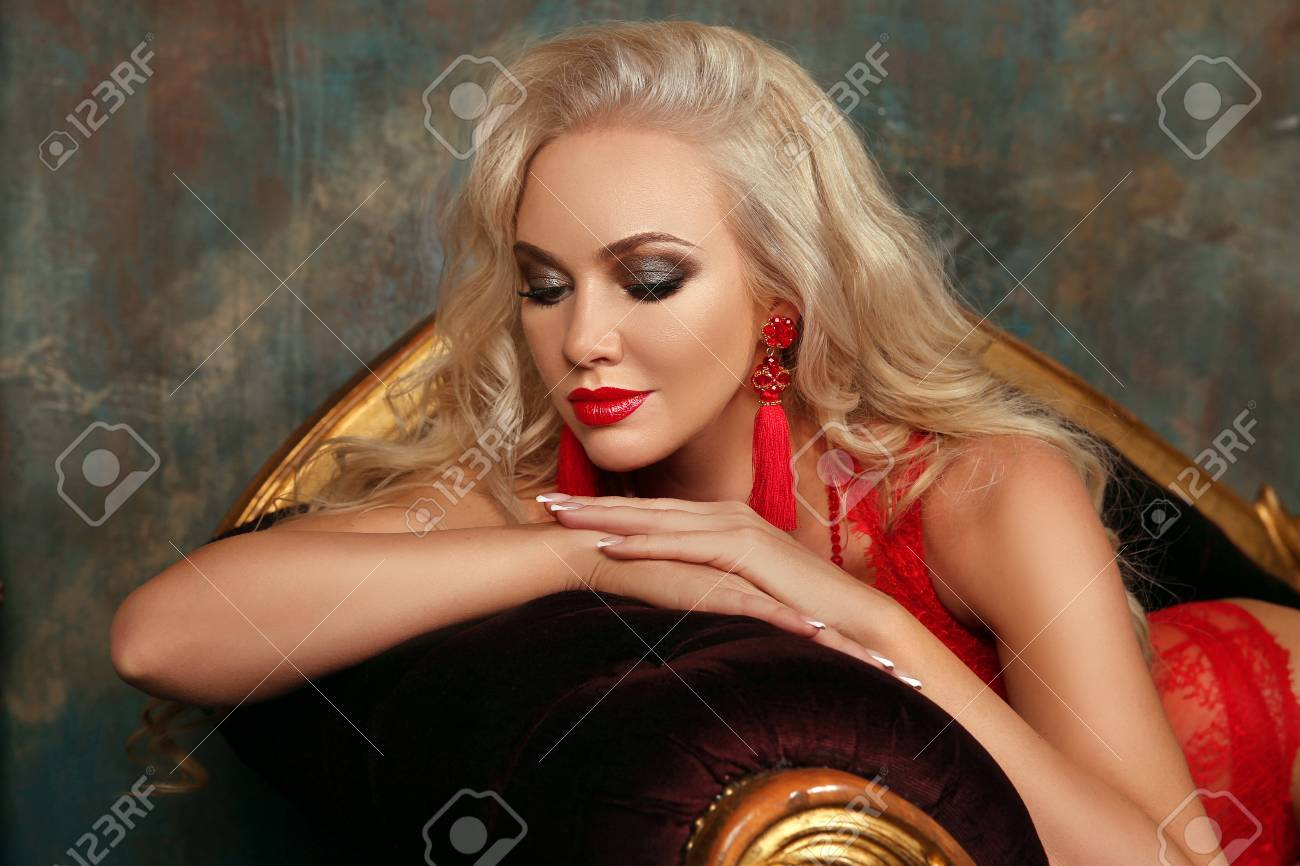 Beauty makeup. Beautiful fashion blond girl model with red lips, fashion earrings, blonde