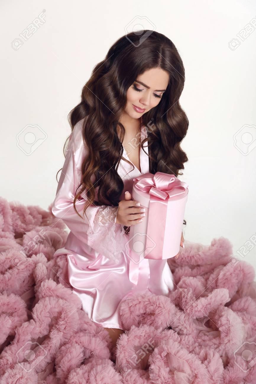 Schönheit welliges Haar. Hübsches Brünette Mädchen Porträt. Lange gewellte  Frisur. Bilden. Attraktive junge Frau, die Hutbox mit rosa Bogen hält.